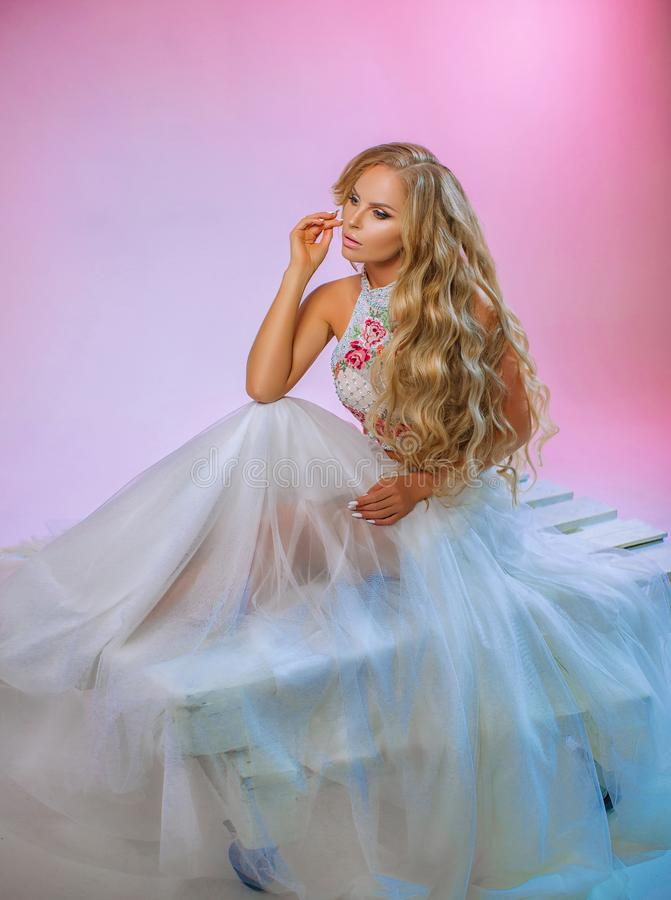 Beautiful blonde with long hair. Young woman in wedding dress on pink background in Studio stock image