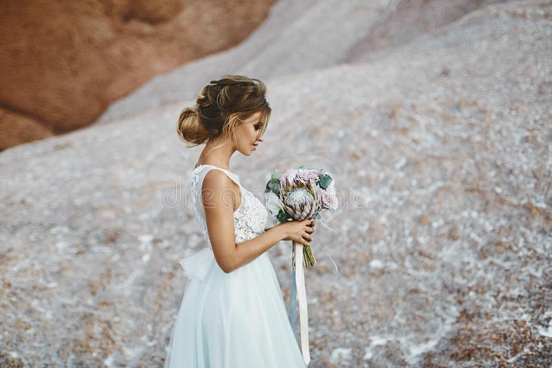 Beautiful blonde model girl with modeling wedding hairstyle in a fashionable white lace dress with a bouquet of exotics stock photos