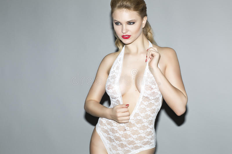 beautiful blonde model in studio wearing a white body stocking royalty free stock photo