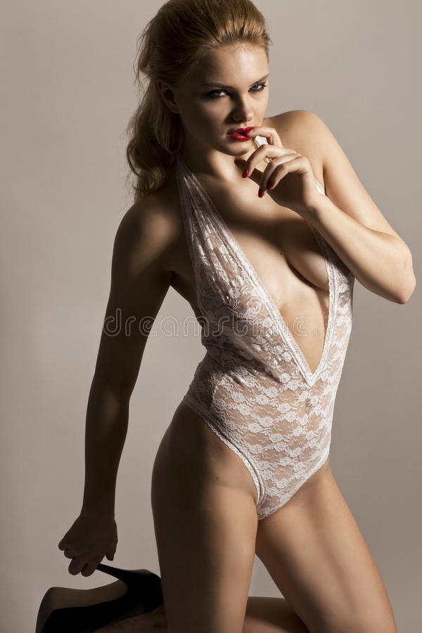 Beautiful blonde model in studio wearing a white body stocking royalty free stock images