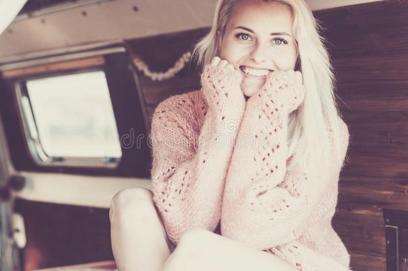 Beautiful blonde model white caucasian skin with beauty face smile at you looking at the camera. sit down in a van with wood stock images