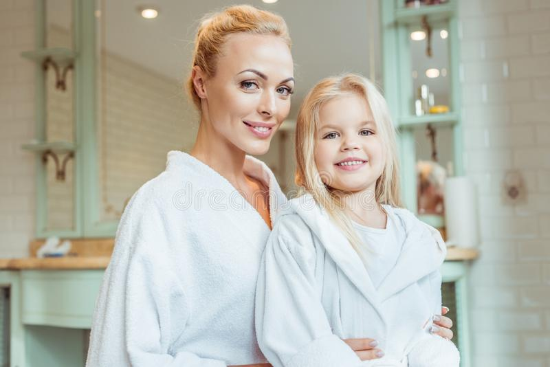 beautiful blonde mother and daughter in bathrobes smiling at camera royalty free stock photos