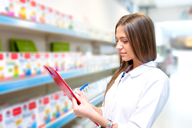 Beautiful blonde pharmacist in drugstore or pharmacy stock photography