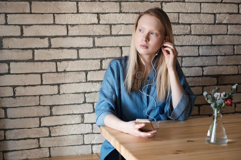 Beautiful blonde with a phone in her hand, touched the earpiece in the ear wearing in blue shirt at the cafe table stock photos