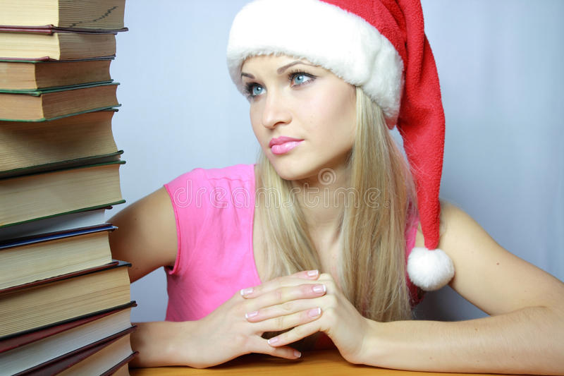 Beautiful blonde in red hubcap with books. Sexual and beautiful blonde in red hubcap with books royalty free stock photos
