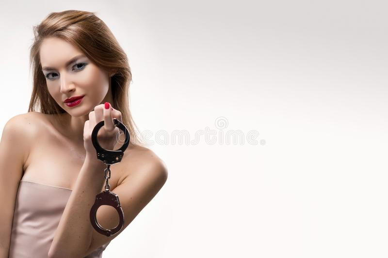 The beautiful blonde red lips girl smiles and holds handcuffs on stock image