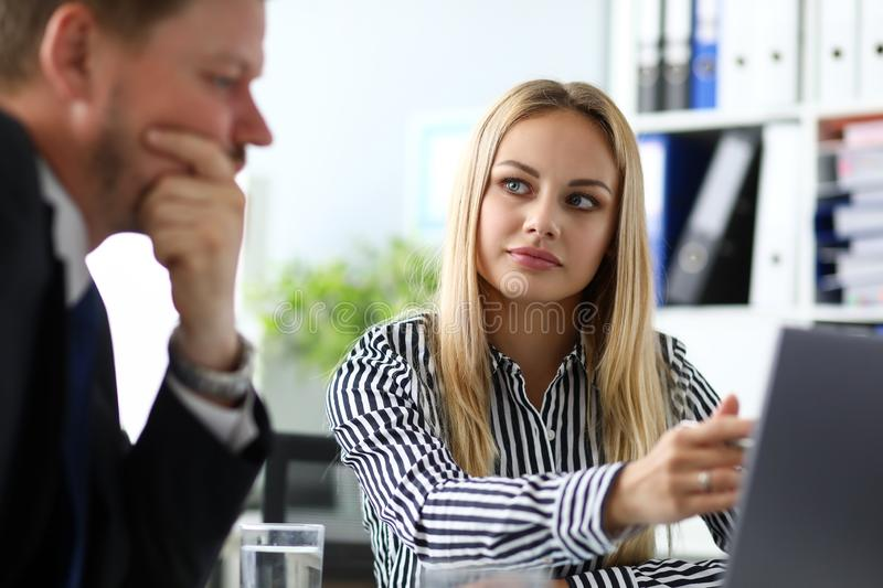 Beautiful blonde secretary sitting at workplace talking with boss stock photos