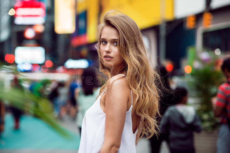 Beautiful blonde tourist girl walking in busy city street with long hair flying on the wind. Woman looking at camera outdoors royalty free stock photos