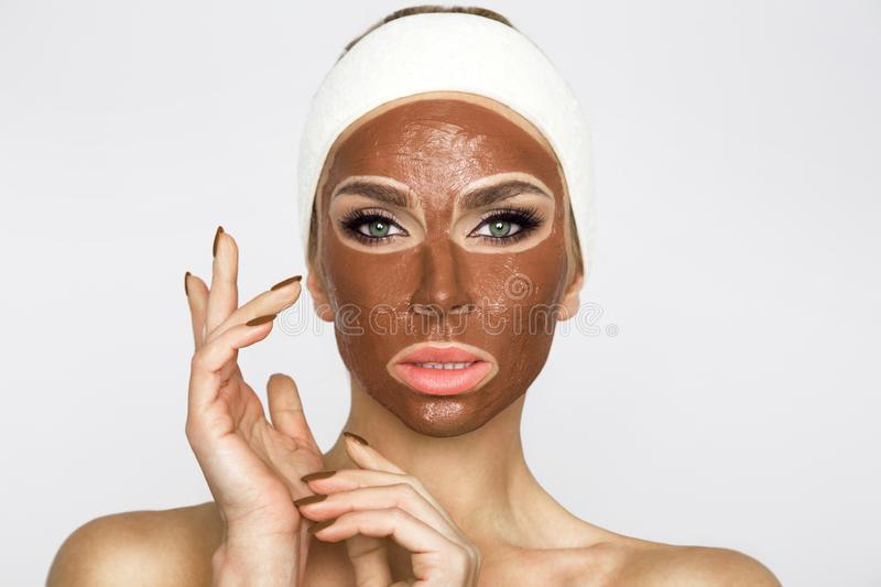 Beautiful blonde woman with a facial mask, beauty spa.Chocolate face mask. Beautiful blonde woman model with a facial mask, beauty spa.Chocolate face mask stock photo