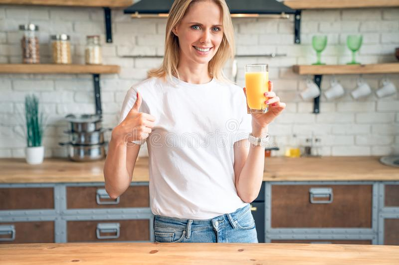Beautiful blonde shows thumb up looking at camera while holding orange juice in her hand and smiling. Health Care And Beauty royalty free stock images
