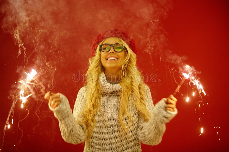 Beautiful blonde with sincere smile holds sparklers in her hands, expresses joyful mood and anticipation of holiday. Wears white sweater and red hat, stands on royalty free stock photos