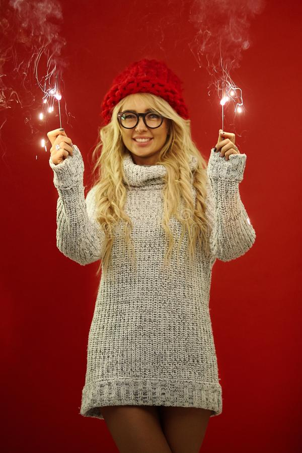 Beautiful blonde with sincere smile holds sparklers in her hands, expresses joyful mood and anticipation of holiday. Wears white sweater and red hat, stands on stock photography