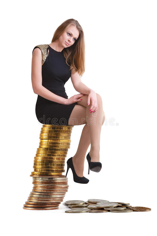 The beautiful blonde sits on a column of coins. The beautiful blonde in short black dress sits on a column of Russian coins royalty free stock photography