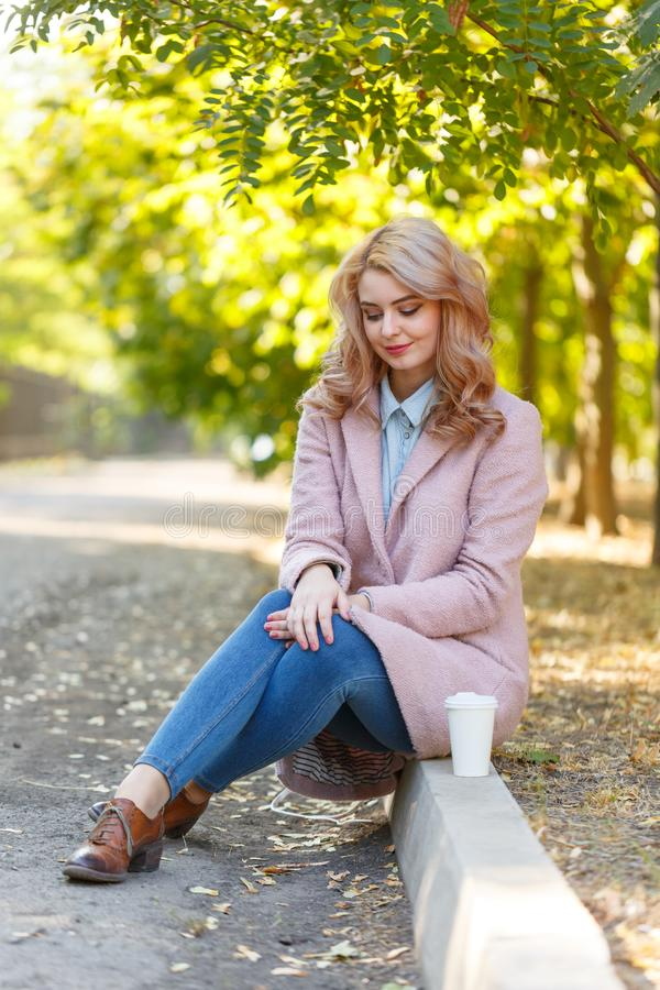 Beautiful blonde is sitting on the curb in the park with coffee. royalty free stock images