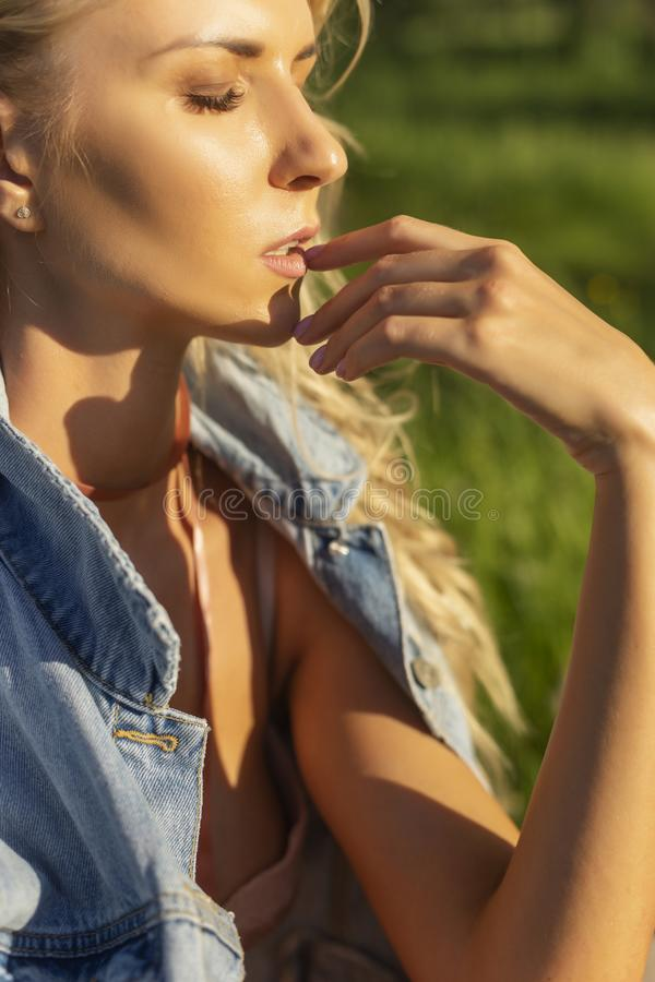 Beautiful blonde slim girl wearing pink lingerie and jeans jacket sits on the grass in the park outdoors. Summer sunny lifestyle. Photo. Advertising and stock photography