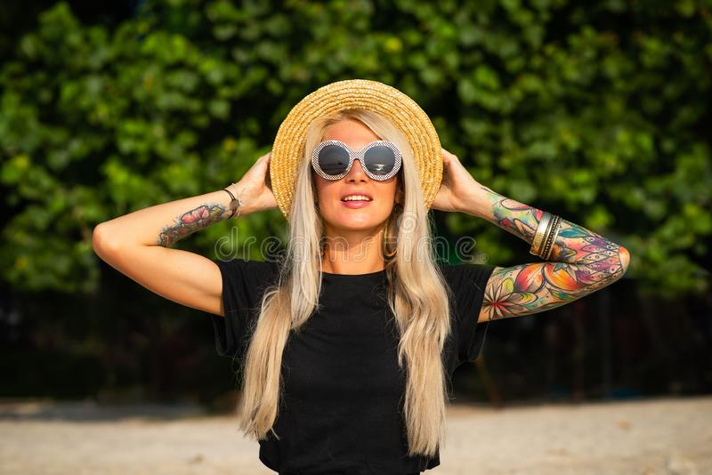 Beautiful blonde is smiling and looking at the morning sea. Holds a hat with his hands with tattoos. Travel to Thailand. Beautiful blonde is smiling and looking royalty free stock images