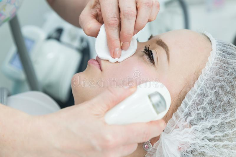 Removing wrinkles on the face and neck with massage. A beautiful blonde smooths wrinkles on the face and neck area with the help of LPG massage in the beauty stock photography
