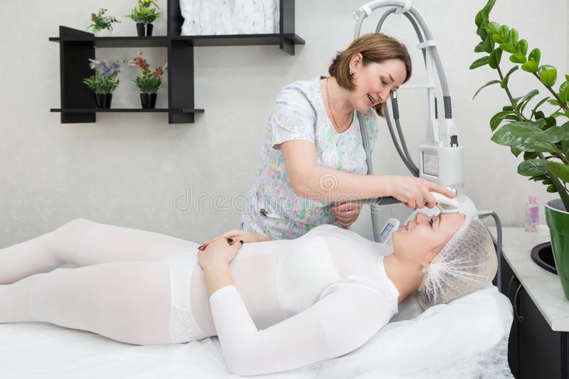 Removing wrinkles on the face and neck with massage. A beautiful blonde smooths wrinkles on the face and neck area with the help of LPG massage in the beauty stock image