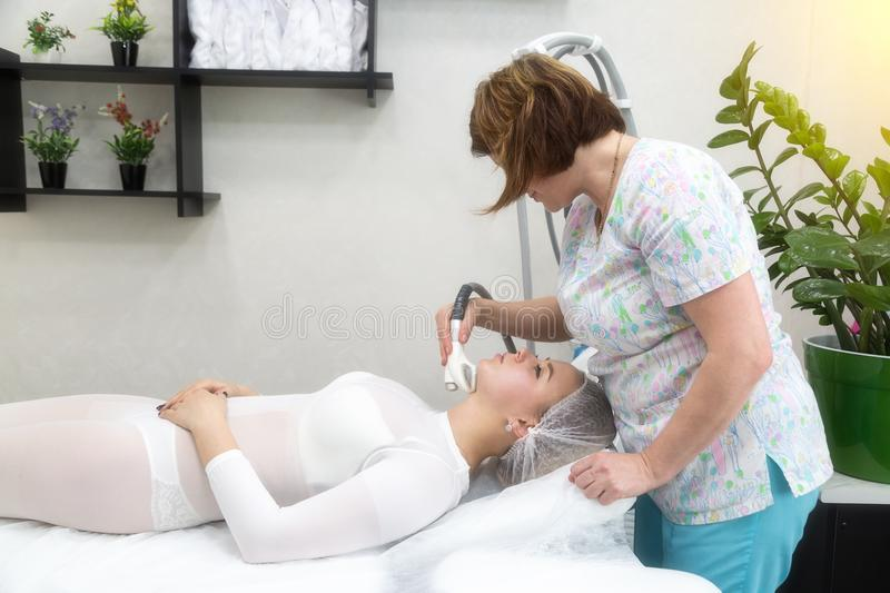Removing wrinkles on the face and neck with massage. A beautiful blonde smooths wrinkles on the face and neck area with the help of massage in the beauty salon stock photo