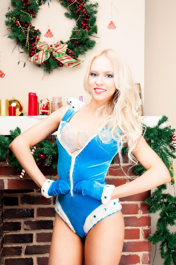 Beautiful blonde Snow Maiden young woman in a blue suit and gloves at the Christmas tree a brick fireplace. New year, christm royalty free stock photography