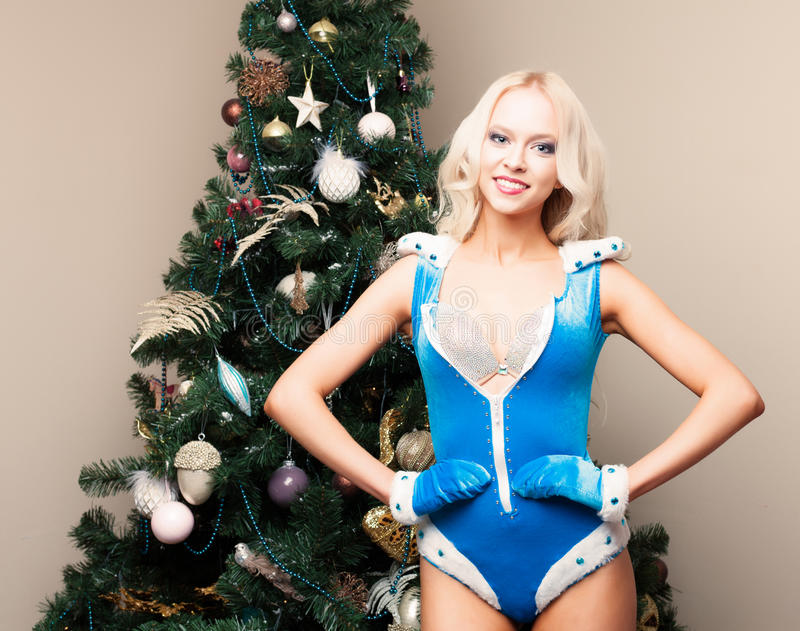 Beautiful blonde Snow Maiden young woman in a blue suit and gloves at the Christmas tree. New year, christmas, x-mas, new yea royalty free stock photography