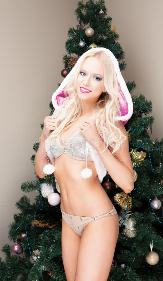 Beautiful blonde Snow Maiden young woman in a pink suit and hood at the Christmas tree. New year, christmas, x-mas, new stock photography