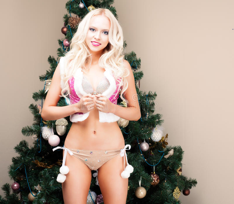 Beautiful blonde Snow Maiden very young woman in a pink suit and hood at the Christmas tree. New year, christmas, x-mas, new royalty free stock photography