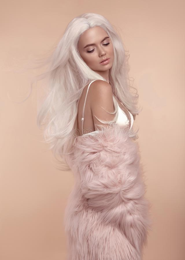 Beautiful blonde stylish woman in fashion winter clothes. Fashionable girl wearing pink fur coat isolated on beige studio ba royalty free stock images