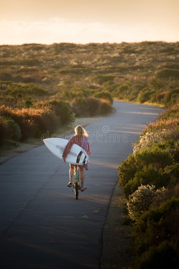 Beautiful blonde surfer girl on her way to the beach on her bicycle with her surfboard. royalty free stock image