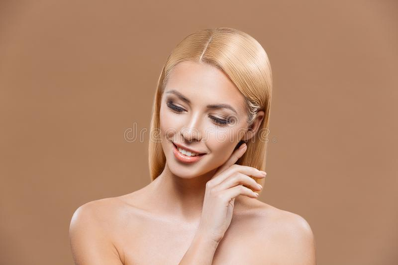 Beautiful blonde tender woman with perfect skin,. Isolated on brown royalty free stock photo