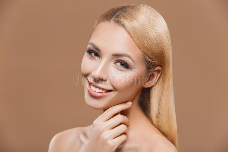 Beautiful blonde tender woman with perfect skin,. Isolated on brown stock image