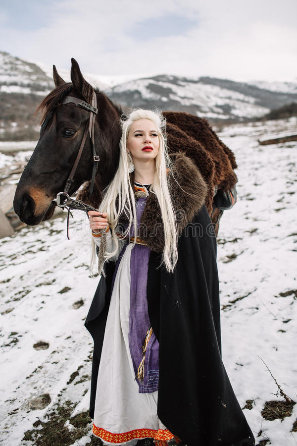 Beautiful blonde Viking in a black cape on horseback stock photography