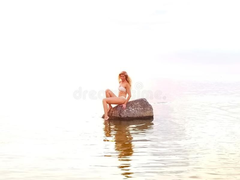beautiful blonde in a white bikini sits on a stone standing in the water during sunset stock image