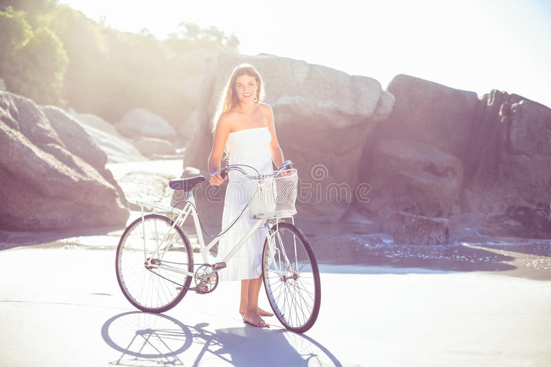 Beautiful blonde in white sundress standing with bike on the beach royalty free stock images