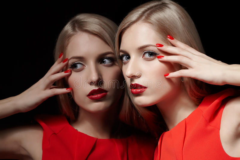 Beautiful blonde woman. Portrait of young beautiful long-haired blonde woman in red dress standing close to mirror and touching her face with manicured fingers royalty free stock image