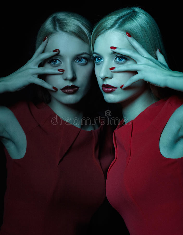Beautiful blonde woman. Portrait of beautiful young blonde woman in teal lighting at mirror royalty free stock photography