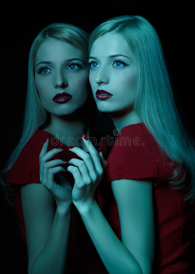 Beautiful blonde woman. Portrait of beautiful young blonde woman in teal lighting posing at mirror stock photo