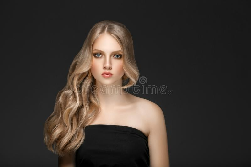 Beautiful Blonde Woman Beauty Model Girl with perfect makeup over black background. stock image