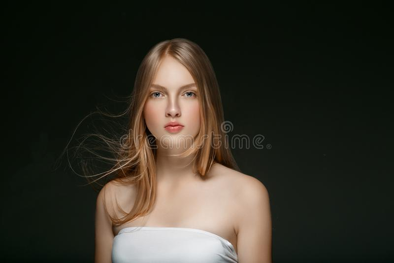 Beautiful Blonde Woman Beauty Model Girl with perfect makeup over black background. Beautiful Blonde Woman Beauty Model Girl with perfect makeup and hairstyle stock image