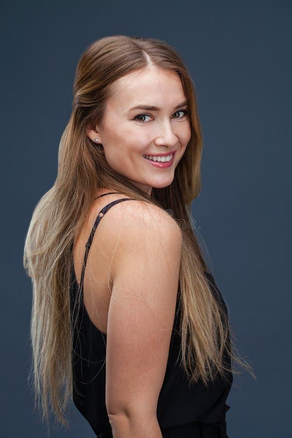 Beautiful blonde woman in black dress royalty free stock photo