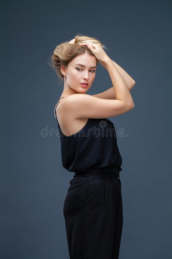 Beautiful blonde woman in black dress stock photos