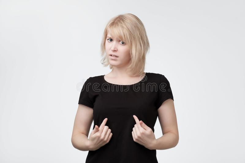 Beautiful blonde woman in a black shirt pointing at herself to say It was not me. I am not guilty stock photo
