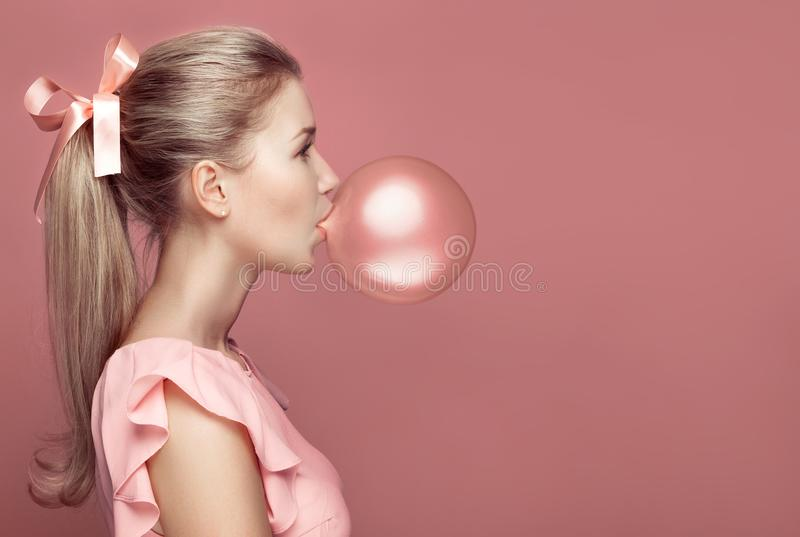 Beautiful blonde woman blowing gum. Fashion portrait royalty free stock image