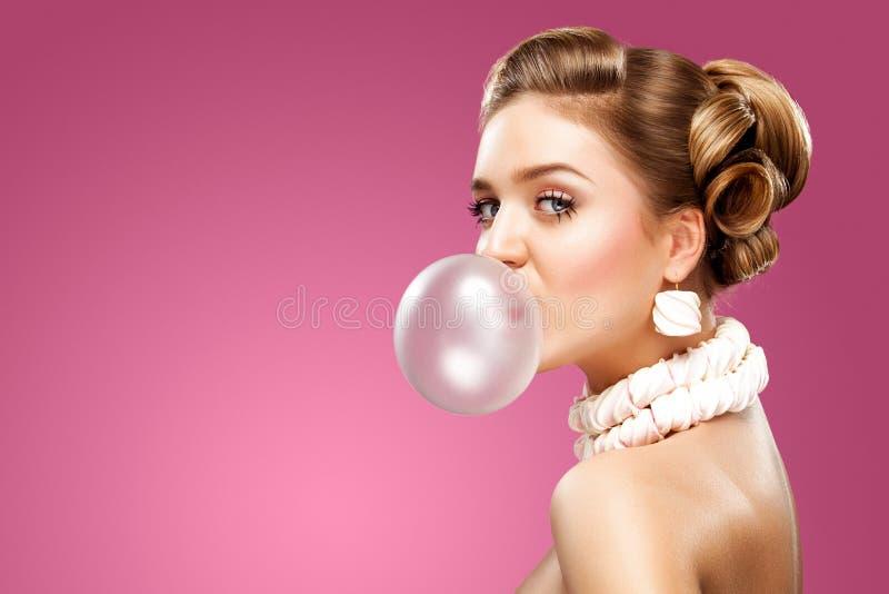 Beautiful blonde woman blowing pink bubble gum. Fashion portrait. stock photo