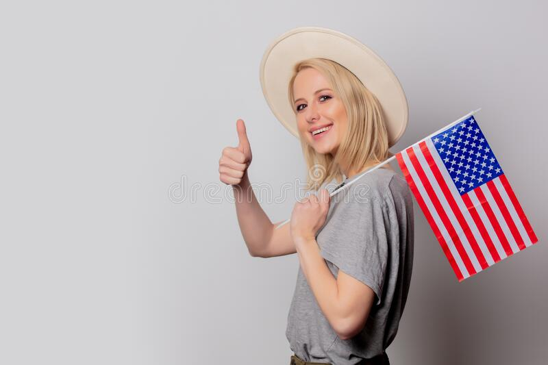 Beautiful blonde woman in cowboy hat with USA flag on white background stock photos