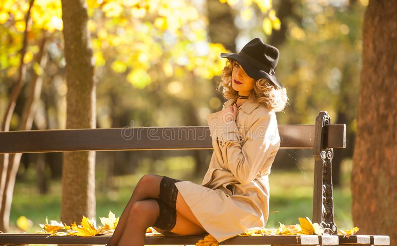 Beautiful blonde woman with cream coat , long legs and black hat in a autumn scene . Portrait of a very beautiful Elegant and sensual woman with curly hair ans stock photography