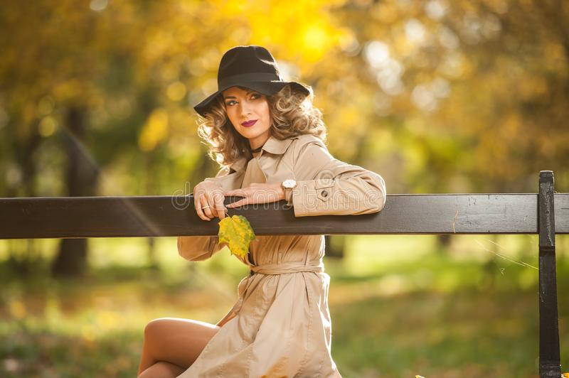 Beautiful blonde woman with cream coat , long legs and black hat in a autumn scene . Portrait of a very beautiful Elegant and sensual woman with curly hair ans royalty free stock image