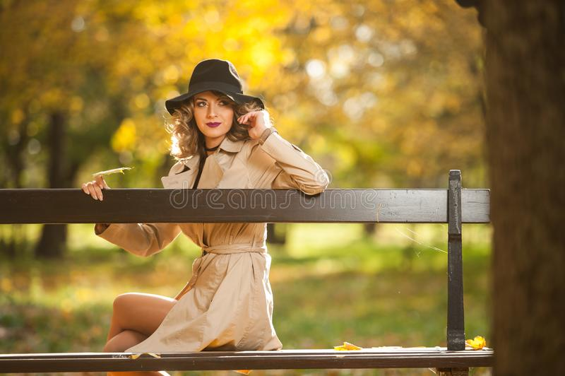 Beautiful blonde woman with cream coat , long legs and black hat in a autumn scene . Portrait of a very beautiful Elegant and sensual woman with curly hair ans stock images