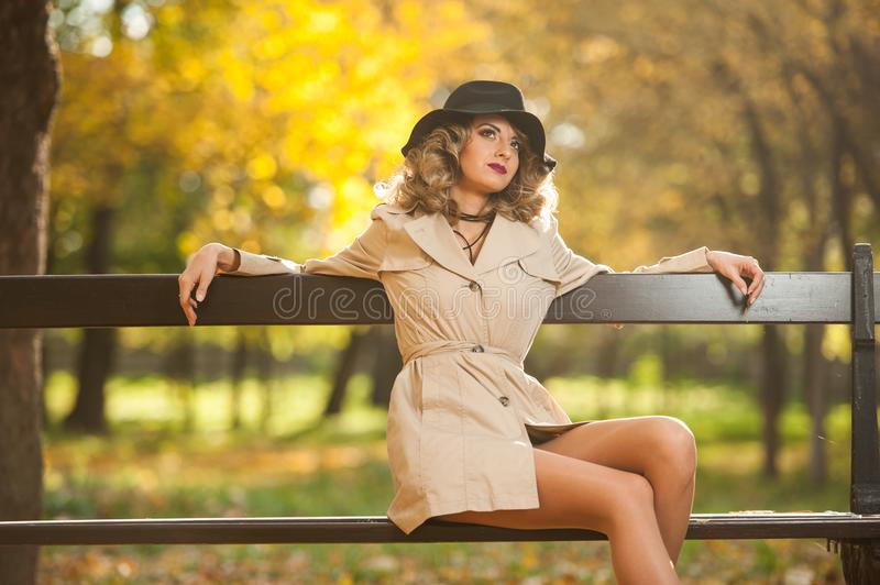 Beautiful blonde woman with cream coat , long legs and black hat in a autumn scene . Portrait of a very beautiful Elegant and sensual woman with curly hair ans royalty free stock photo