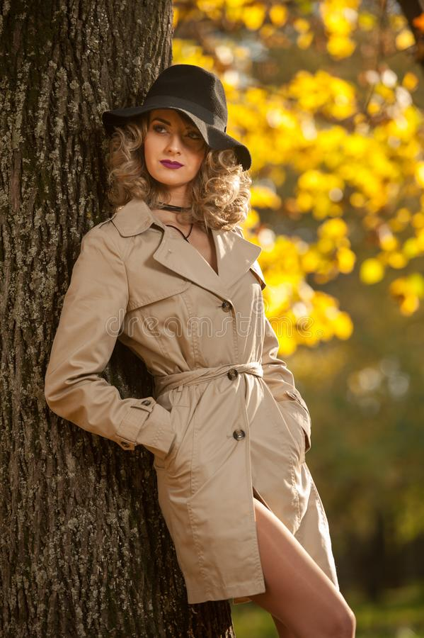 Beautiful blonde woman with cream coat , long legs and black hat in a autumn scene . Portrait of a very beautiful Elegant and sensual woman with curly hair ans royalty free stock images